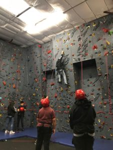 6 people, four of which are wearing red helmets, at a rock climbing wall. One person is climbing.